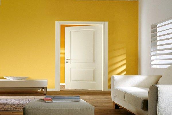 una porta aperta di color bianco e un divano di color beige