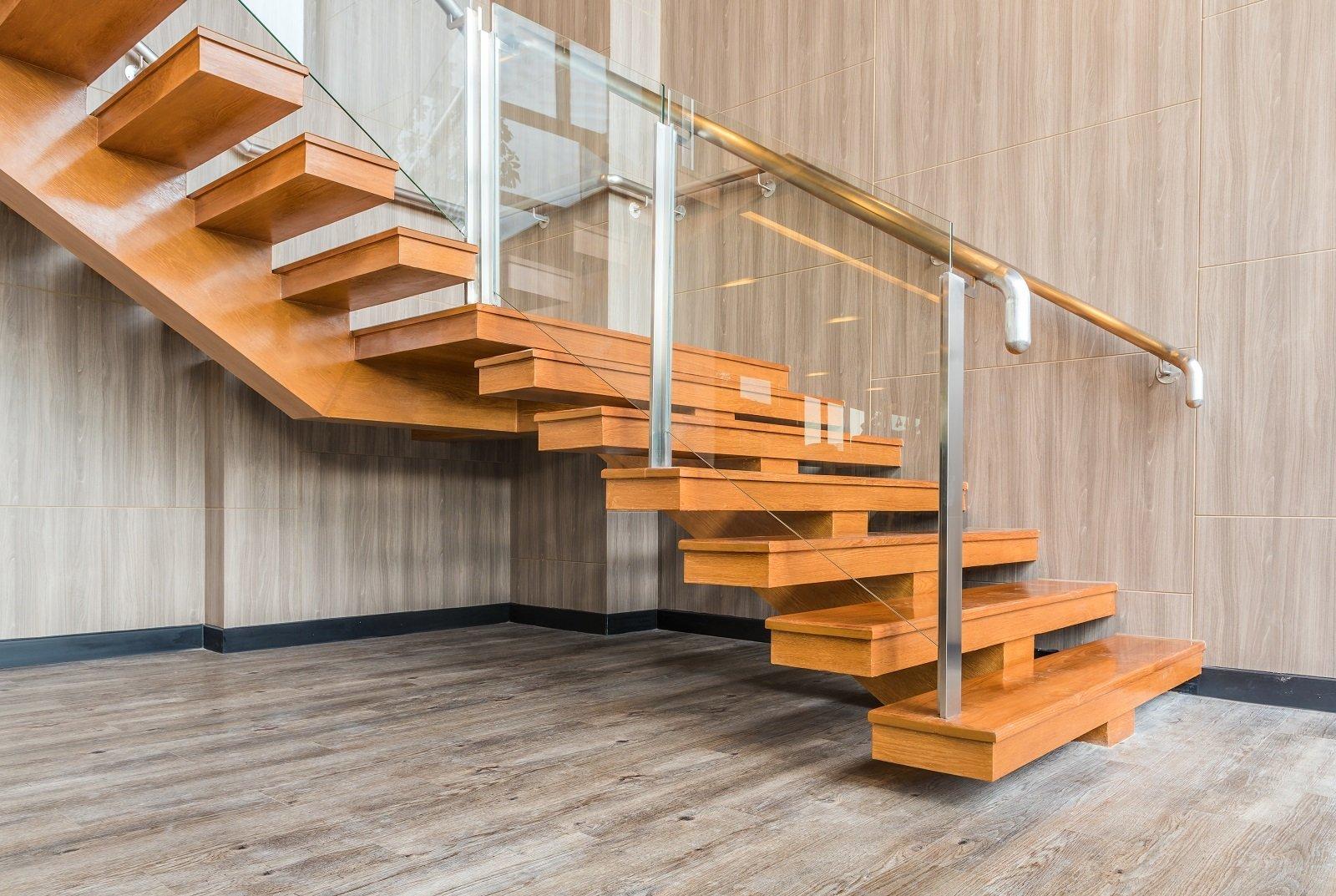delle scale con gradini in legno e corrimano in vetro e ferro