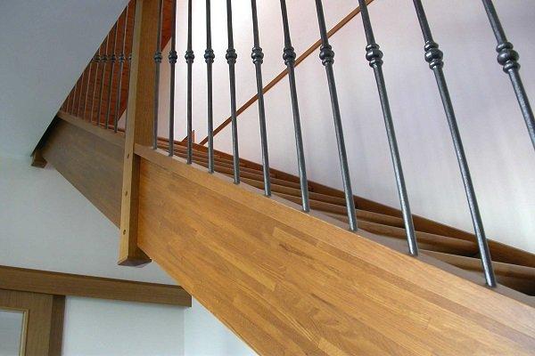 delle scale in legno con una ringhiera in ferro battuto