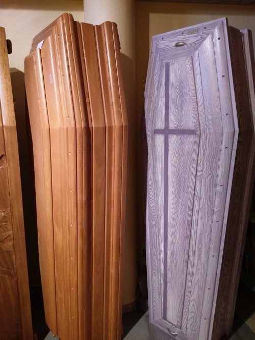 delle bare in legno marrone e una di color grigio