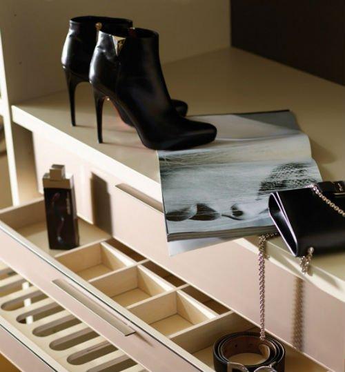 delle scarpe di pelle nera appoggiate su una rivista e una borsetta