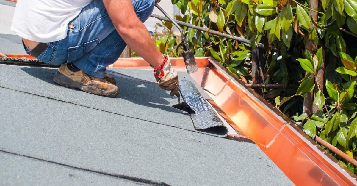 una mano di un operaio che copre un soffitto con un telo di isolamento