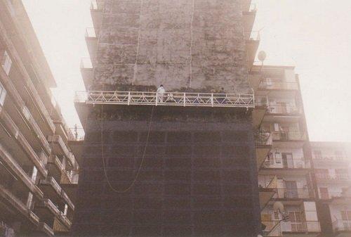 Un uomo su una piattaforma davanti a uno stabile in fase di ristrutturazione
