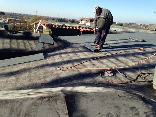 Un uomo in piedi che guarda un rotolo di tessuto impermeabilizzante  posto sulla pavimentazione di un tetto