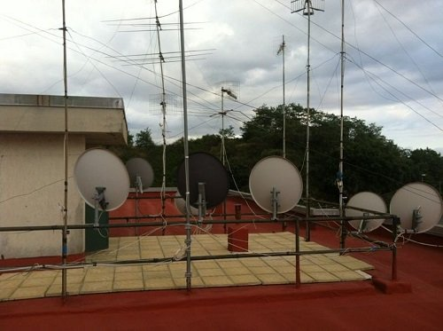 Delle parabole e antenne su una ringhiera posta su un tetto