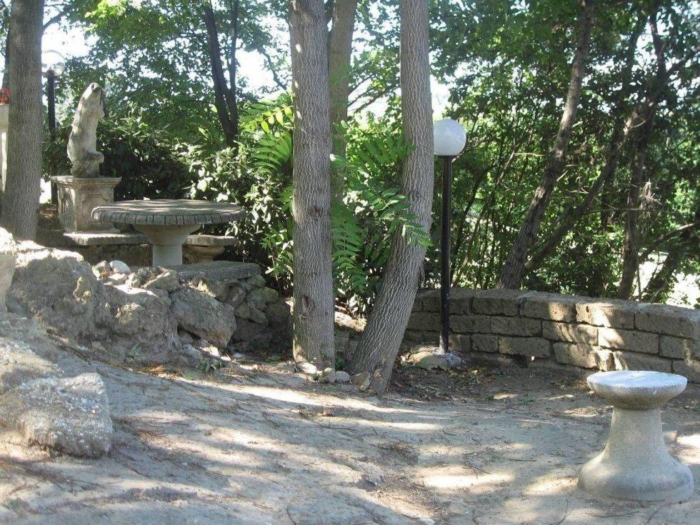 Statua di pietra, tavola, banche... un luogo per rilassarsi