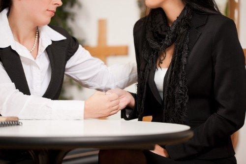 Una donna consolando altra mentre le prende la mano