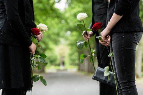 Due donne e due uomini sostenendo ciascuno una rosa bianca o rossa a la mano