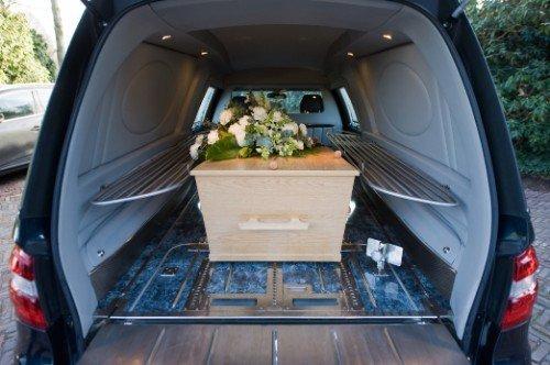 Bara di legno chiaro all'interno del carro funebre coperta di fiori bianchi
