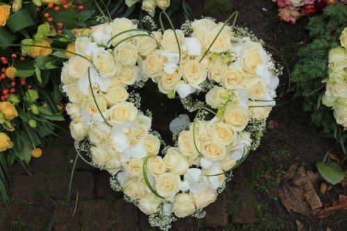 Corona in forma di cuore fatta con gigli bianchi e rose gialle