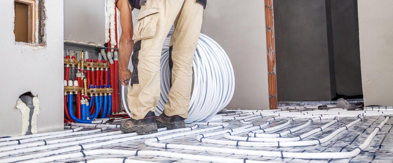 operaio durante di installazione del tubi montato per riscaldamento a pavimento di una casa