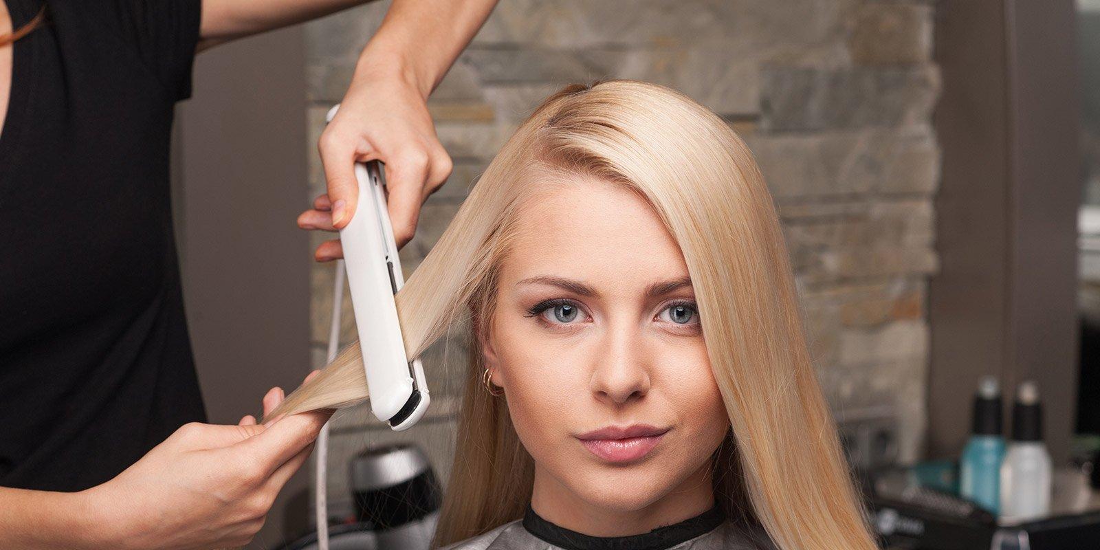 Parrucchiere usa piastra lisciante su capelli biondi