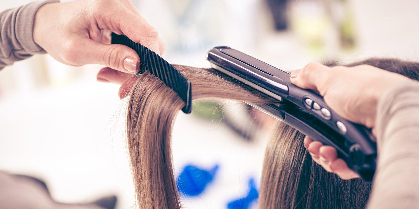 Primo piano di piastra lisciante su capelli castani