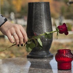 Placing a rose on a gravestone