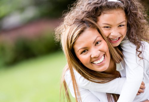 A women and a child smiling in field in Vancouver