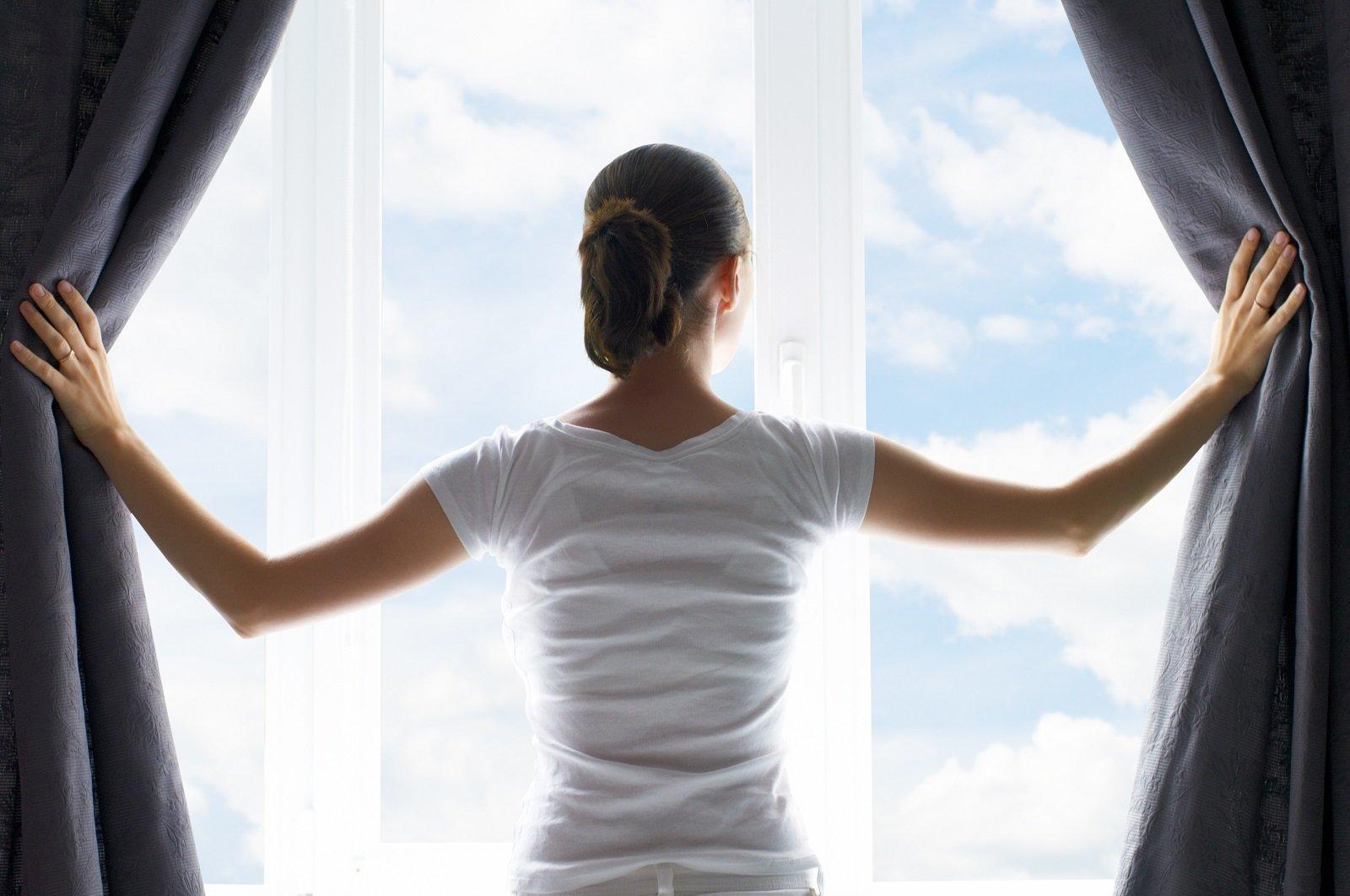 Donna che apre le tende di una finestra in pvc bianca