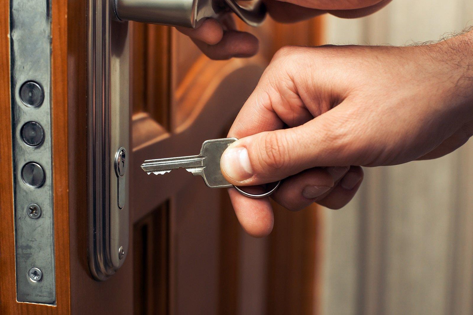 mano che apre una porta con la chiave