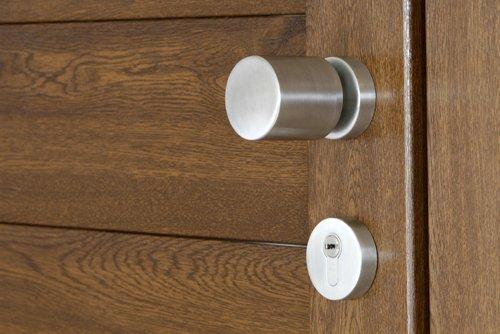 Dettaglio della serratura e maniglia in acciaio di una porta in legno