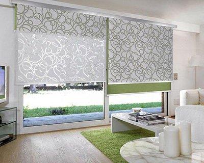 una finestra con delle tende a pannello di color verde e disegni