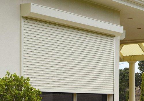 una finestra con la tapparella meta' aperta di color bianco