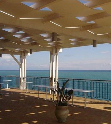 una terrazza con una pergola e vista del mare