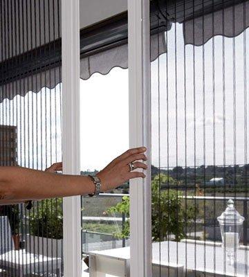 una mano che apre una porta finestra con ante scorrevoli