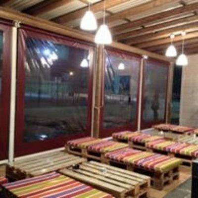 dei bancali in legno con cuscini colorati e delle vetrate