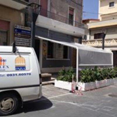 un furgone bianco e vista di un tendone da esterno con dei vasi e delle piante