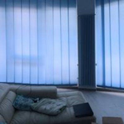 un divano con dei cuscini e vista delle tende alle finestre
