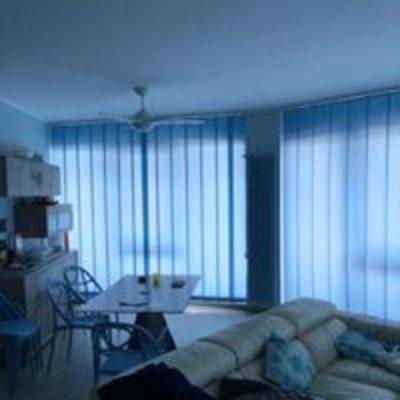 una stanza con un divano, un tavolo con delle sedie e delle tende alle  finestre