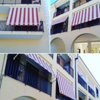 delle tende da esterno di colore bianco e rosso su dei balconi