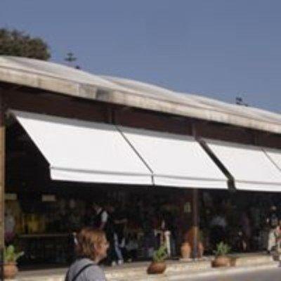 delle tende bianche e sotto delle persone in un negozio all'aperto