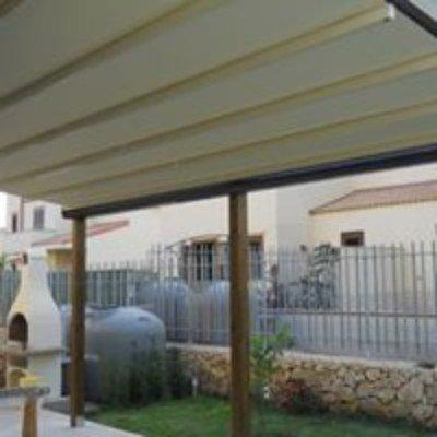 una copertura con vista di un giardino e un muretto con una ringhiera