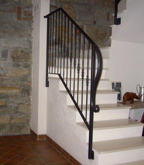delle scale e un corrimano in ferro battuto di color nero