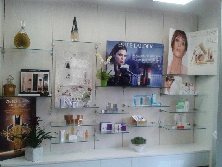 Parete con scaffali di vetro dove vediamo profumi di marca e prodotti per la pelle