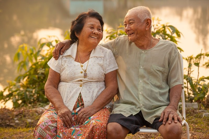 Happy Asian Senior couple sitting outdoors on sunset