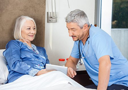 Male caretaker listening to elderly woman on bed