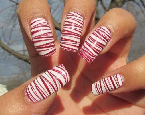 unghie di donna con smalto a strisce bianche e rosse