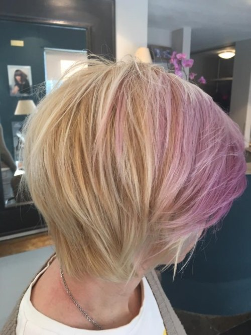una ragazza con capelli biondi e meches rosa