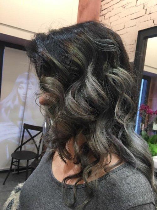 una ragazza con capelli lunghi castani mossi vista di lato