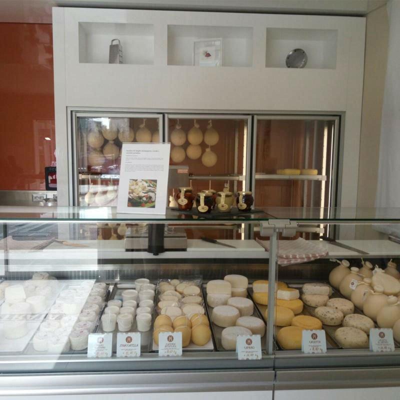 bancone con vari formaggi in esposizione