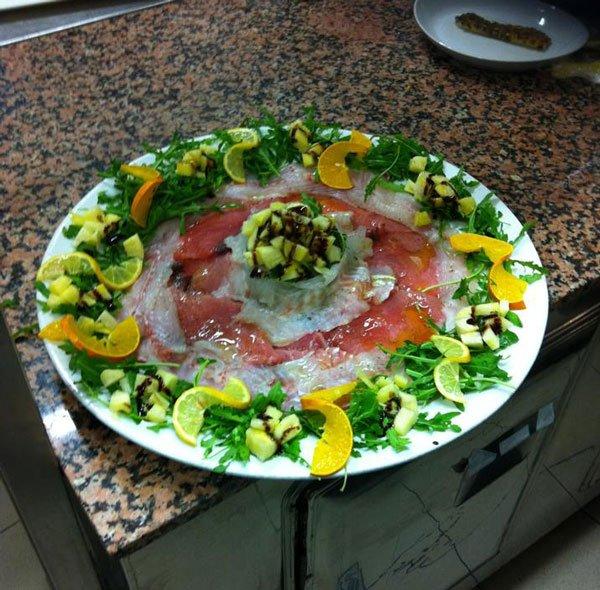 una tartare di pesce con rucola,fette di arancia e limone