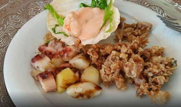 un piatto di fritto di pesce,polipo,patate e gamberetti in salsa cocktail in una conchiglia