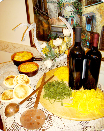 tavola imbandita con due bottiglie di vino e tegamini in terracotta con cibo