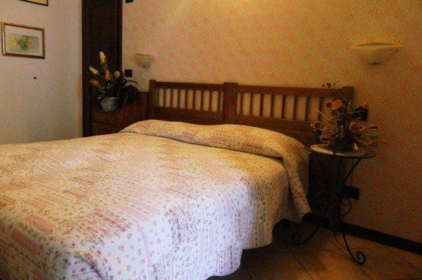 camera da letto con letto matrimoniale e due tavolini con fiori ai bordi