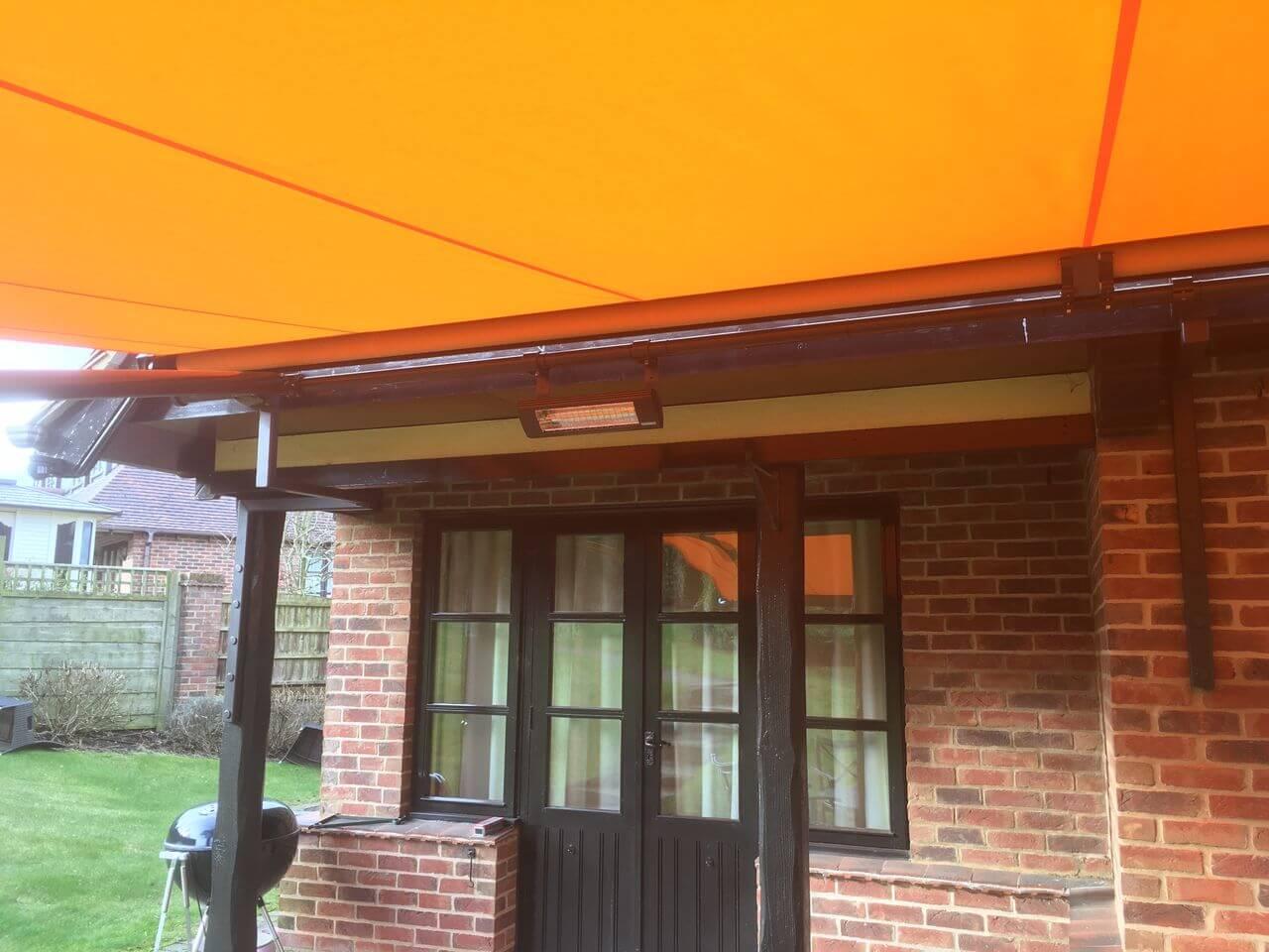 orange fabric markilux awning on custom brackets over patio