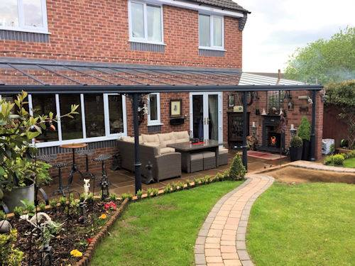 Glass veranda over a paved patio area with garden furniture