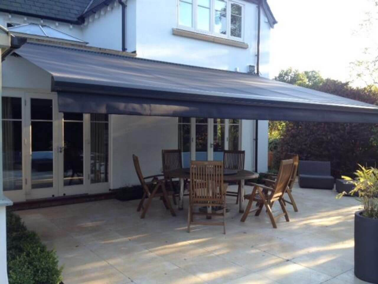 Weinor K2000 electric awning in black over a patio and garden furniture