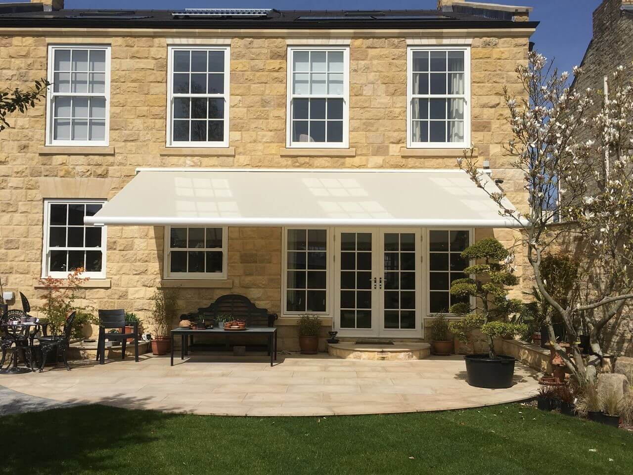 Markilux 6000 electric awning fitted to stone house over a patio