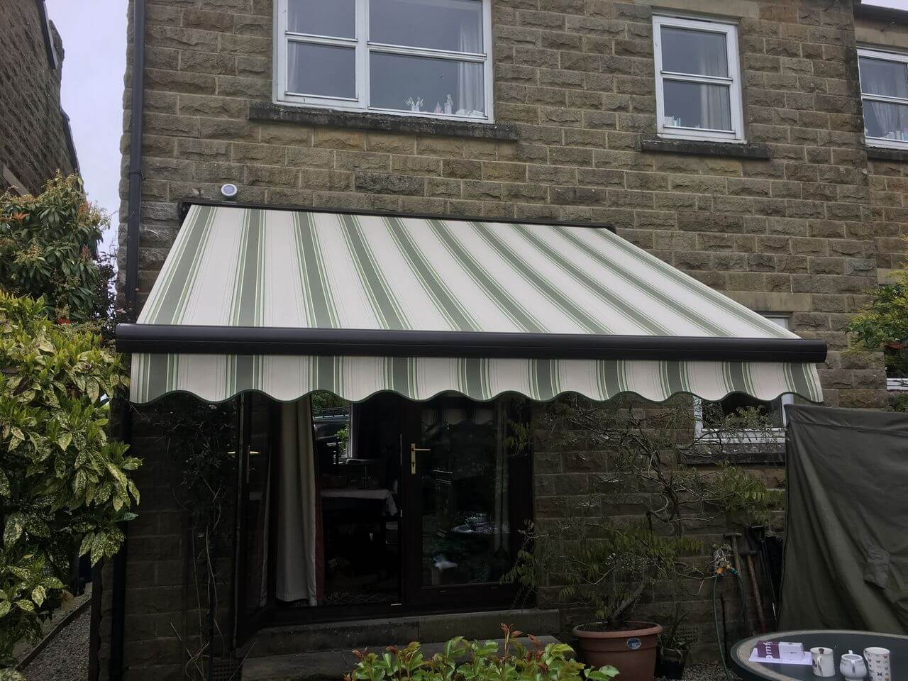 Brown electric harol patio awning fitted to a stone house with french doors
